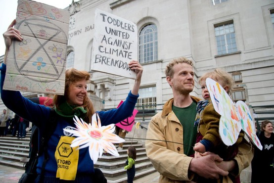 Več sto okoljskih aktivistov se je protestno priklenilo na ograjo urada Merklove