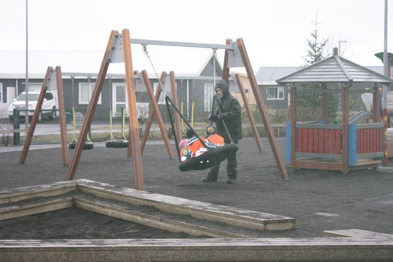 Otroci v vrtcu na Islandiji se gugajo v deževnem in vetrovnem vremenu.