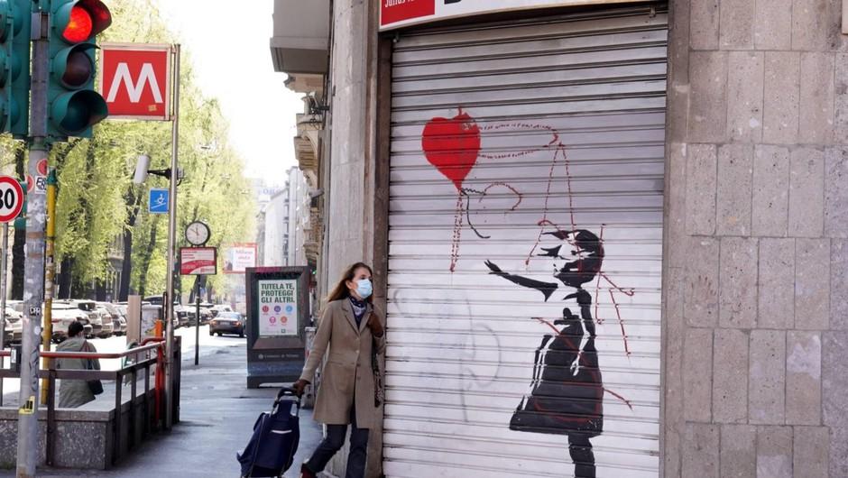 Banksyjeva podoba Dekleta s preluknjanim ušesom na stavbi v Hannovru z zaščitno masko (foto: profimedia)