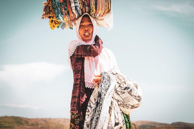Prodajalka tradicionalno spletenih saraongov na plaži Tanjung Aan