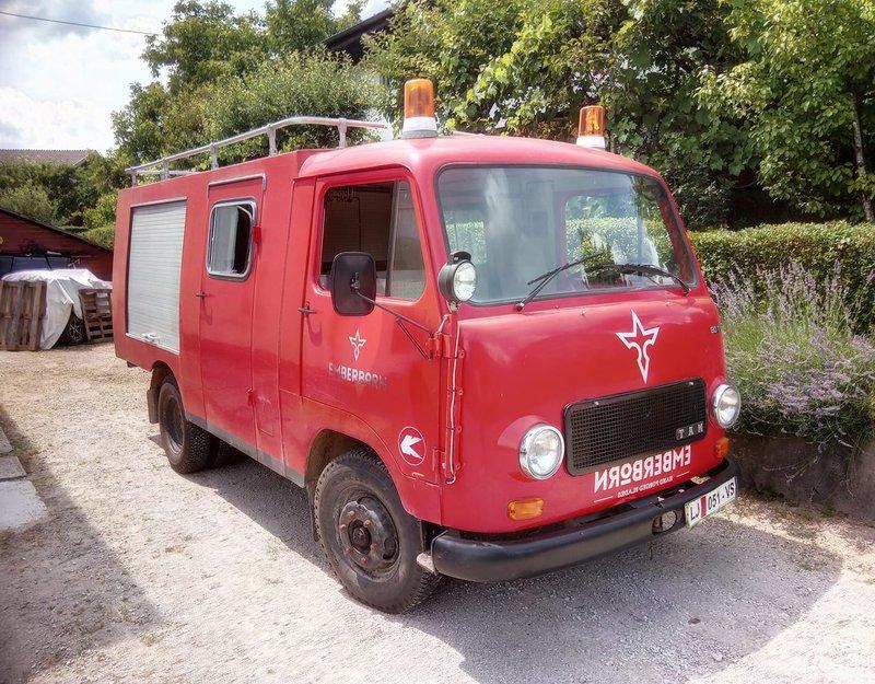 Jugoslovanski gasilski kombi, pobarvan svetlo oranžno in s hudim Emberbornovim logotipom, katerega avtor je Branko Čeak.